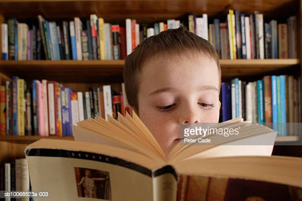 boy (8-9) reading book, close-up - brixton stock pictures, royalty-free photos & images