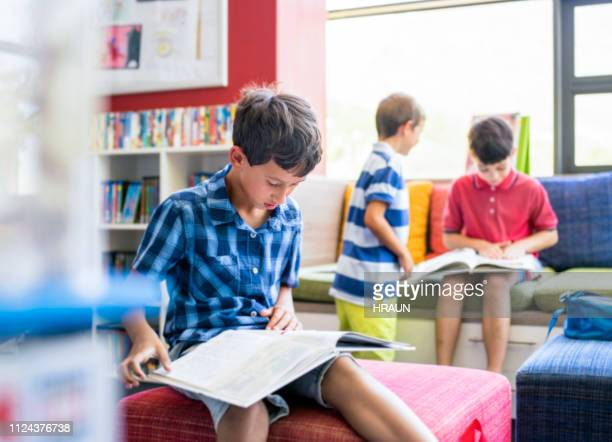 boy reading book in library at elementary school - junior level stock pictures, royalty-free photos & images