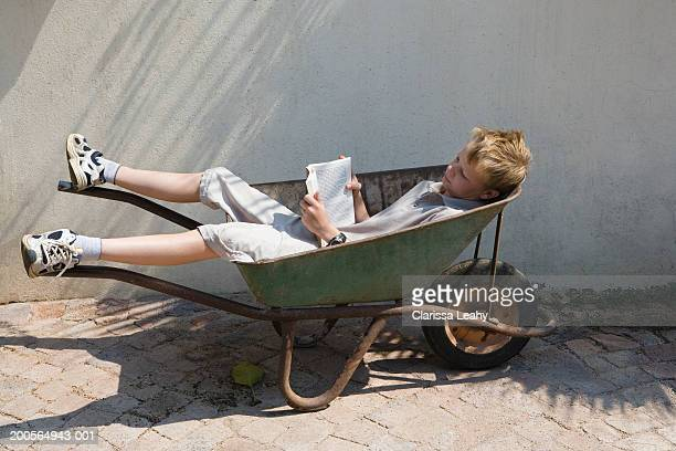 Boy (12-13 years) reading book, lying in wheelbarrow, elevated view