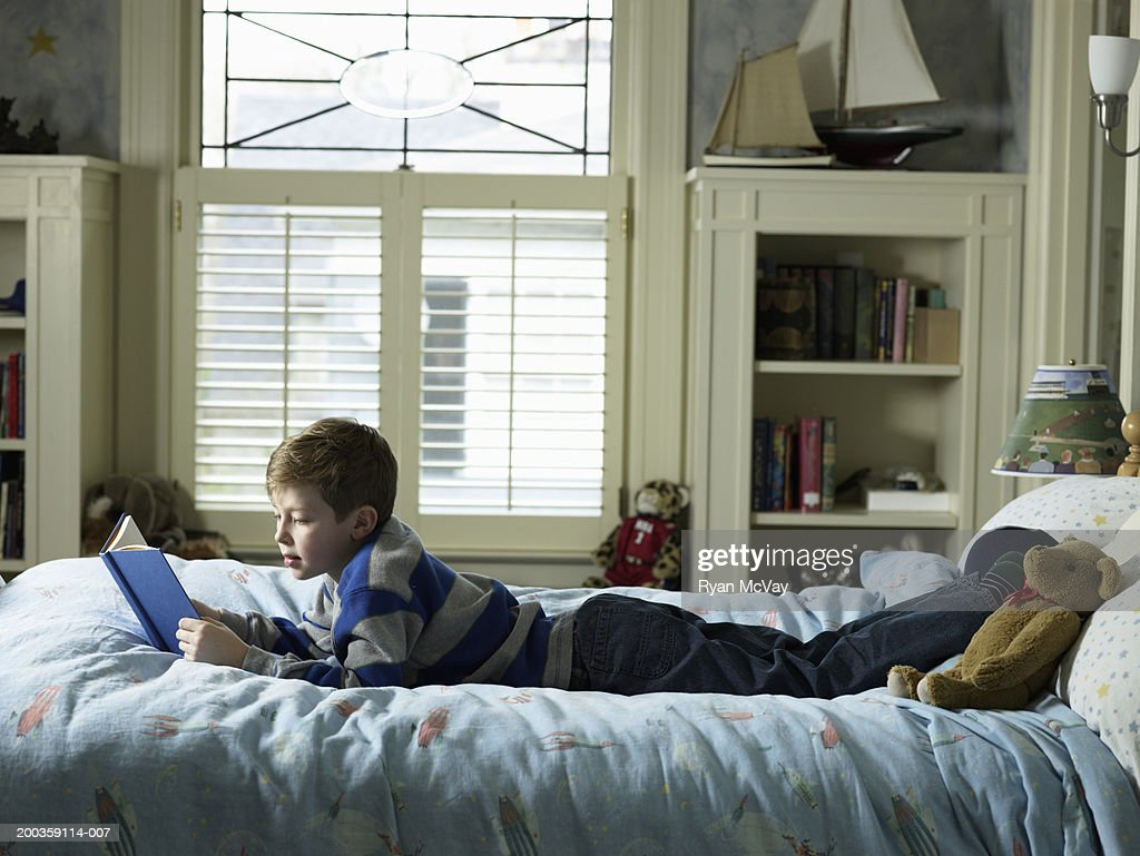 bedroom side view. Boy (7-9) Reading Book On Bed, Side View Bedroom