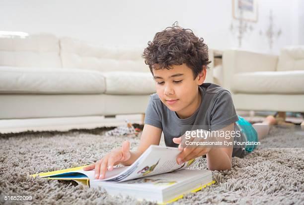 boy reading book on rug in living room - 6 7 años fotografías e imágenes de stock