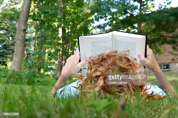 boy reading book - obscured face stock photos and pictures