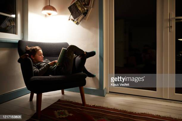 boy reading book under lamp in armchair at night - authenticity stock pictures, royalty-free photos & images