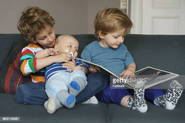 Boy reading book while sitting besides brothers at home