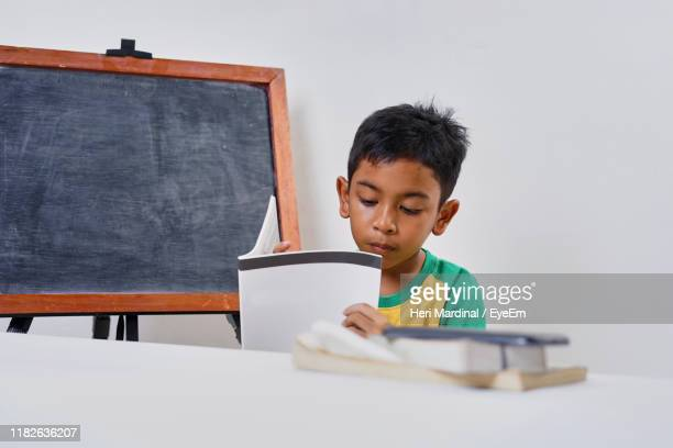 boy reading book while sitting in classroom - heri mardinal stock pictures, royalty-free photos & images