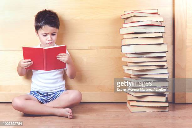 boy reading book while sitting on floor against wooden wall - 読む ストックフォトと画像