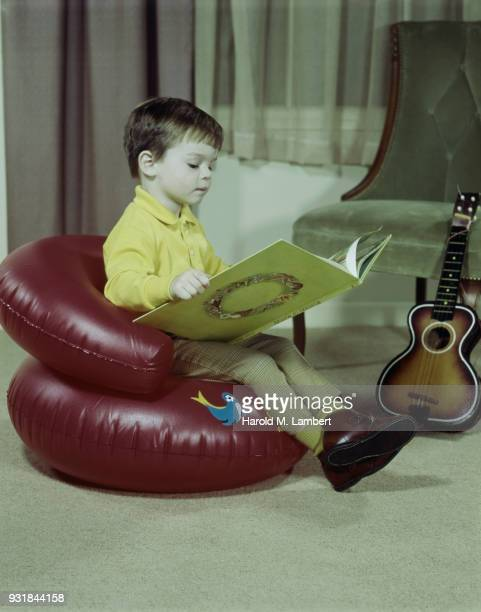 Boy reading book while sitting on inflatable chair