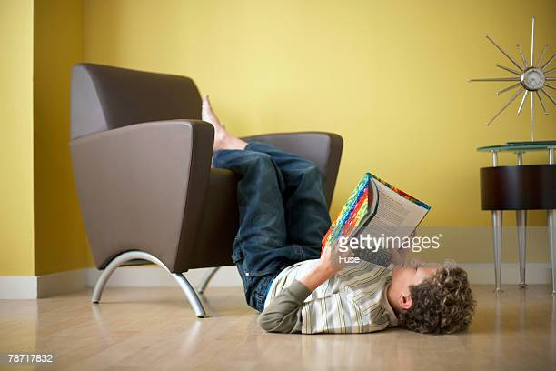 Boy Reading Book with Feet Up