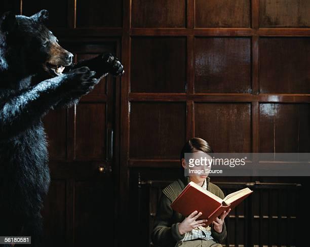 Boy reading by stuffed bear