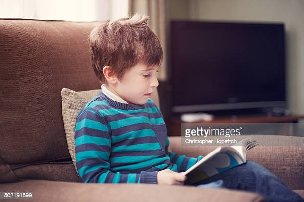 Boy reading by switched off television