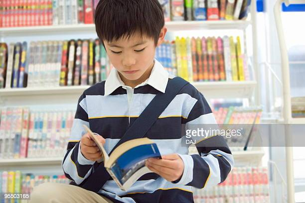 Boy reading comic book at convenience store