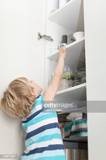 Boy reading for something in cabinet