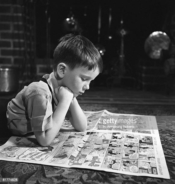 boy reading funnies, indoors. - funny cartoon stock photos and pictures