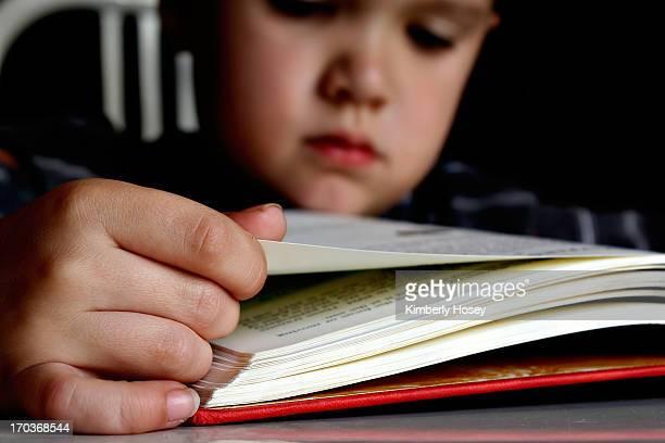 Boy reading hardcover book