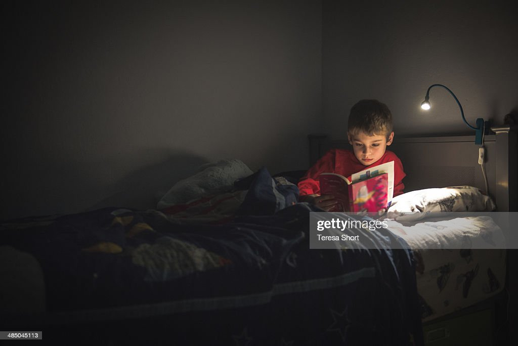 Boy reading in bed with reading lamp : Stock Photo