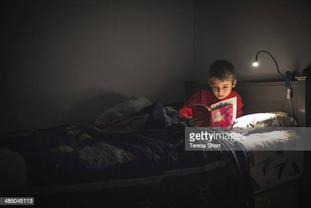 boy reading in bed with reading lamp - electric lamp fotografías e imágenes de stock