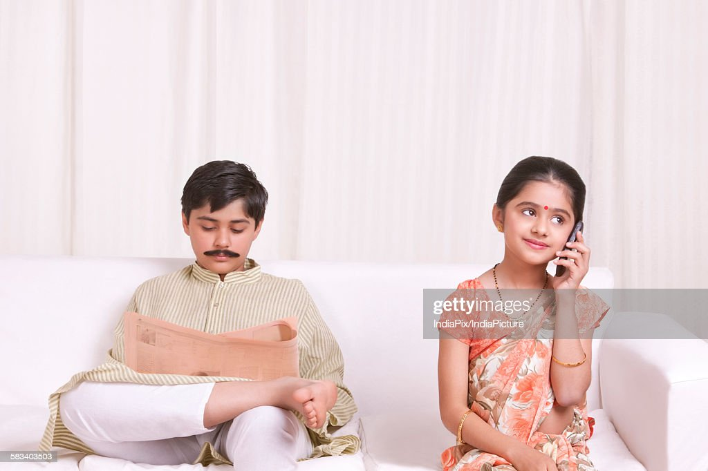 Boy reading newspaper and while girl talks on mobile phone : Stock Photo