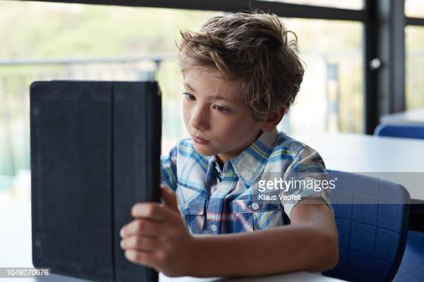boy reading on tablet in classroom - 男子生徒 ストックフォトと画像