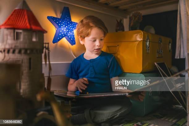 niño leyendo libro de imagen en apartamento loft - cuento de hadas fotografías e imágenes de stock