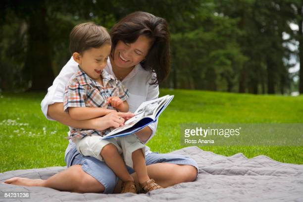 Boy reading story book in park with mother