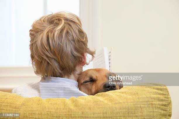 Boy reading whilst cuddling dog