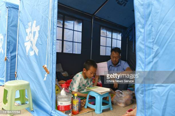 Boy reads a book at a temporary shelter after an earthquake on May 22, 2021 in Yangbi Yi Autonomous County, Dali Bai Autonomous Prefecture, Yunnan...