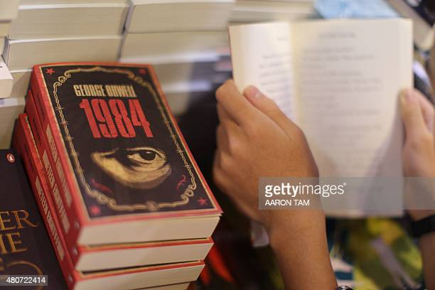 A boy reads a book next to copies of British writer George Orwell's 1984 at Hong Kong's annual book fair on July 15 2015 The 26th edition of the fair...