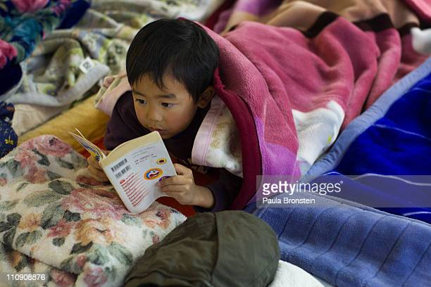 A boy reads a cartoon book at a crowded makeshift evacuation center as hundreds of thousands have become homeless on March 26 2011 in Rikuzentakata...
