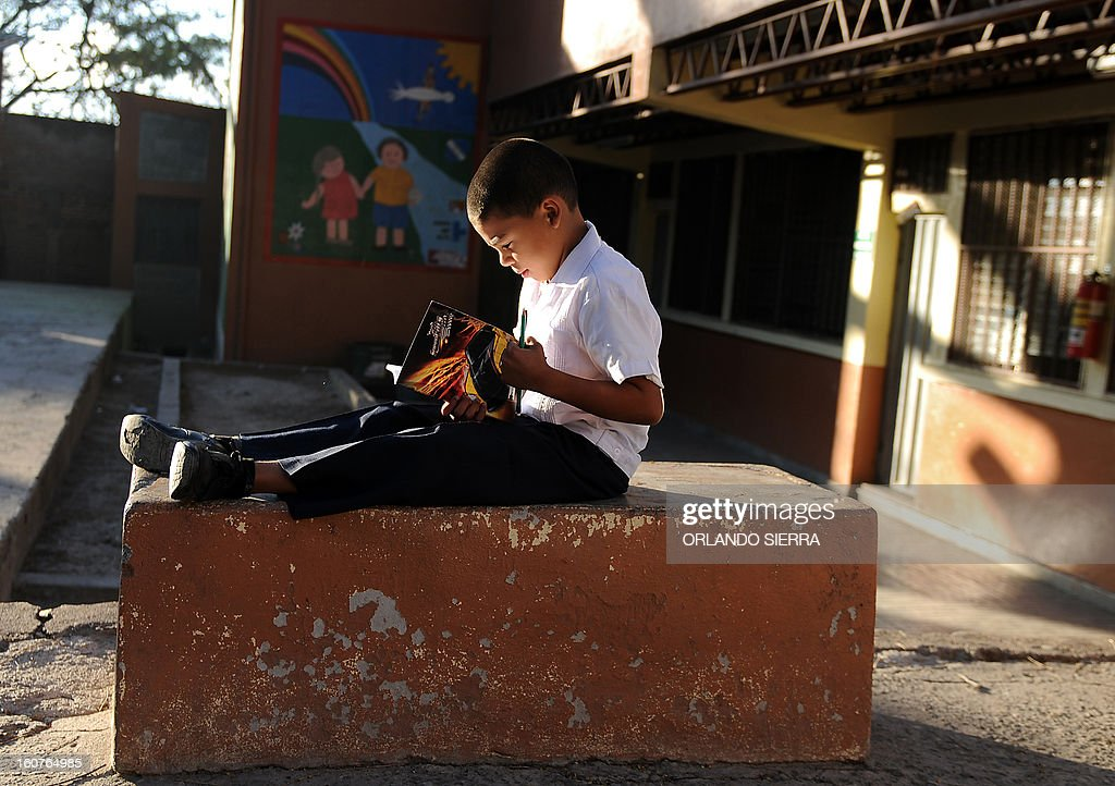 A boy reads at his school in the poor community of Las Ayestas, in Tegucigalpa on February 5, 2013. Honduras' notorious street gangs, especially the Mara 18 and the Mara 13 or Salvatrucha, have imposed a curfew and are charging a 'war tax' in some of the capital's poorest sectors -- thing which led the police to deploy more personnel in theses areas. The violent maras are active in murders, extorsion, drug dealing, arms trafficking and other crimes. The United Nations says Honduras, a country plagued by powerful street gangs and drug-related violence, has the world's highest homicide rate. In 2010 it was 82 per 100,000 inhabitants, and rose to 86 in 2011. By comparison, in drug-cartel-plagued Mexico, for instance, the rate was about 18 in 2010. AFP PHOTO/Orlando SIERRA