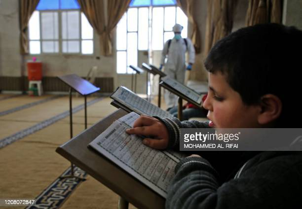 A boy reads from the holy Koran as members of the Syrian Civil Defence disinfect a mosque in the city of Idlib in northwestern Syria on March 23...