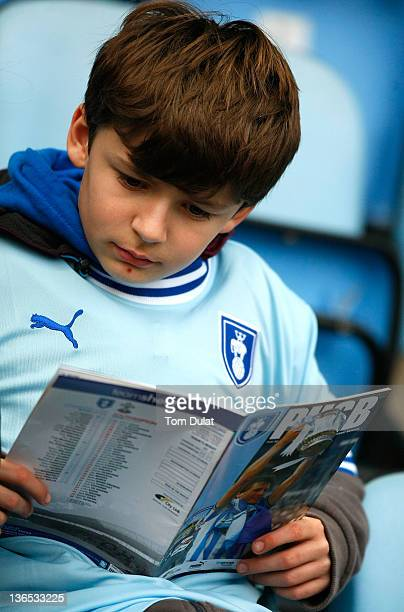 A boy reads his program during the FA Cup 3rd round match between Coventry City and Southampton at the Ricoh Arena on January 07 2012 in Coventry...