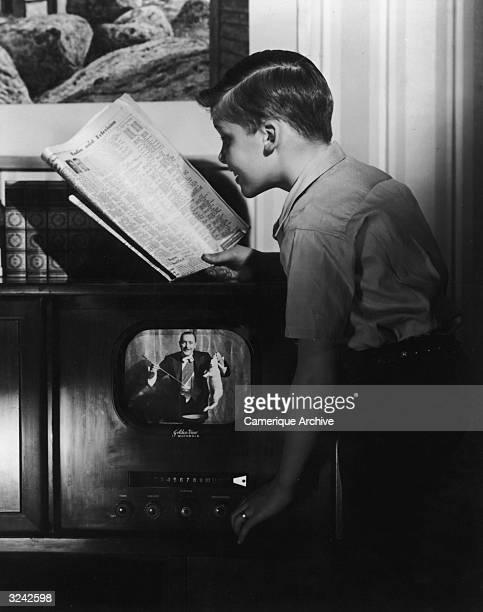 A boy reads the television listings in a newspaper while adjusting the dial on a Motorola 'Golden View' TV set A magician holds a white rabbit and a...