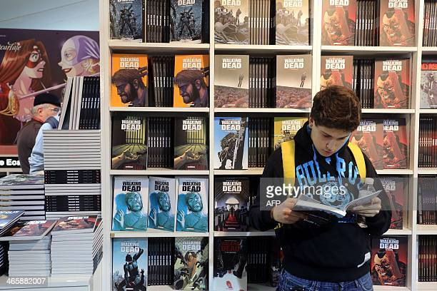 A boy reads the US comic book 'The walking dead' on the first day of the 'Festival international de la bande dessinee' in Angouleme on January 30...