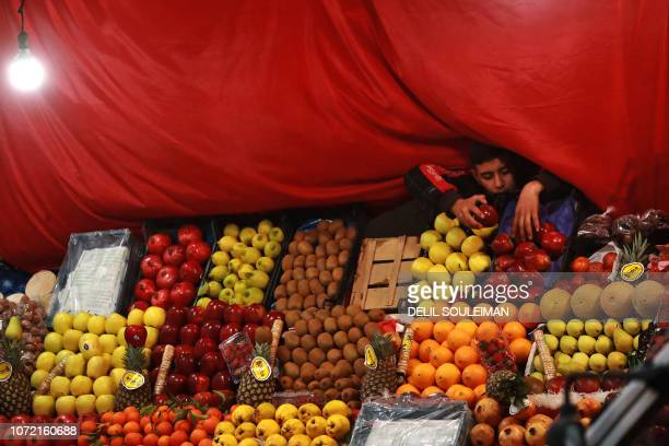 Boy re-arranges apples on display at a fruit seller's stall in a market in the northeastern city of Qamishli on December 12, 2018.