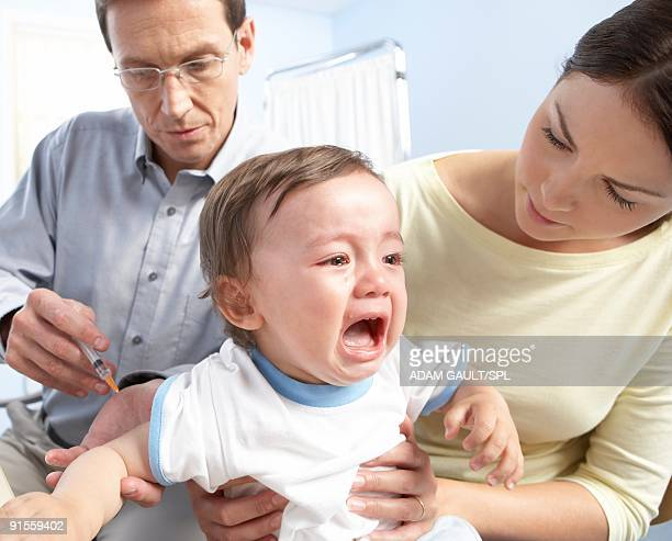 Boy (12-15 months) receiving injection from GP