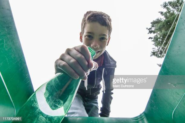 boy recycling plastic bottle - city cleaning stock pictures, royalty-free photos & images