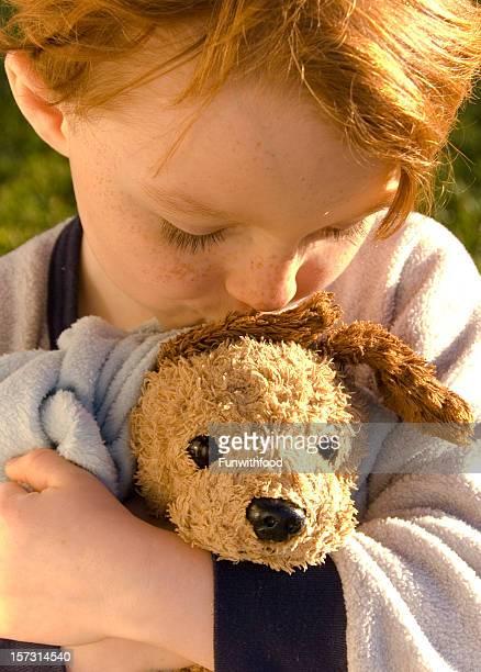 Garçon Redhead en pyjama & couverture, enfant embrassant Chien en peluche