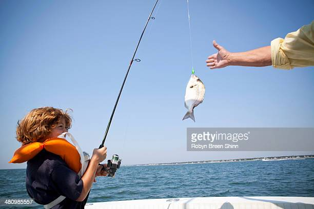 Boy reeling in fish on boat, Falmouth, Massachusetts, USA