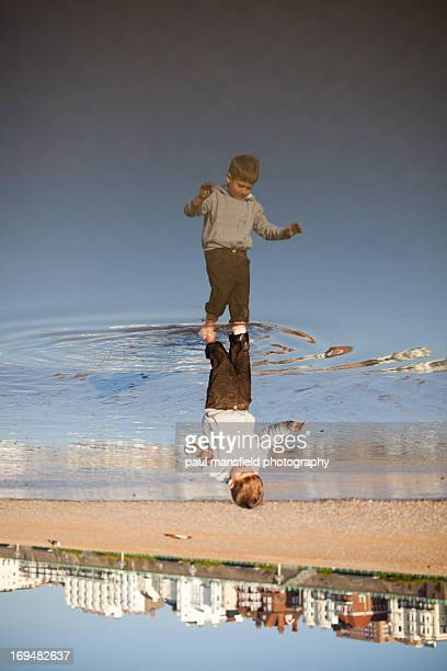 Boy reflected in puddle on Brighton beach