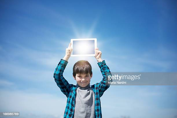 Boy reflecting the sunshine in a digital tablet