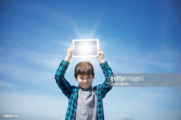 boy reflecting the sunshine in a digital tablet - ein junge allein stock-fotos und bilder