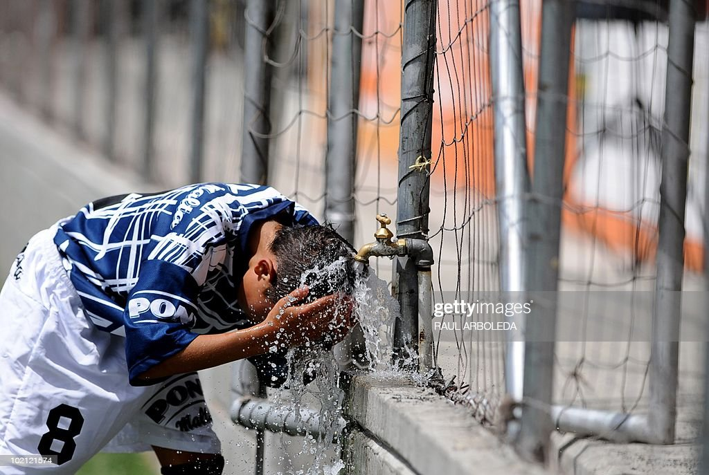 A boy refreshes himself during the 'Mundialito' football tournament in Medellin, Antioquia department, Colombia on June 15, 2010. The 'Mundialito' tournament takes place every four years with the participation of Medellin soccer schools. AFP PHOTO/Raul ARBOLEDA