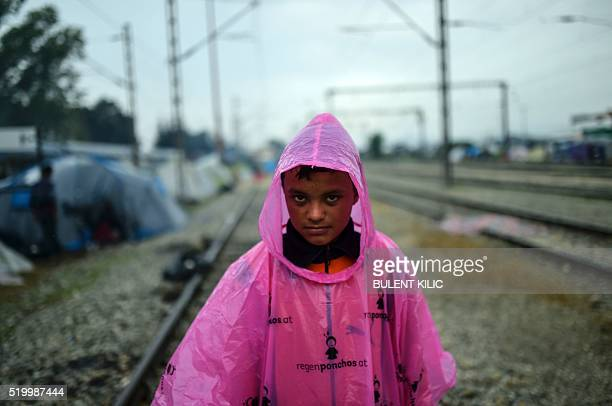 A boy refugee stands under the rain in a makeshift camp in the northern border village of Idomeni Greece on April 9 2016 Four migrant women and a...