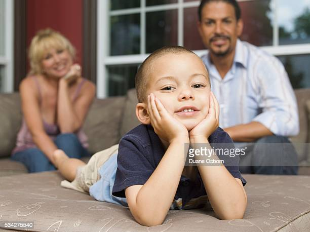 Boy Relaxing, Father and Grandmother in Background