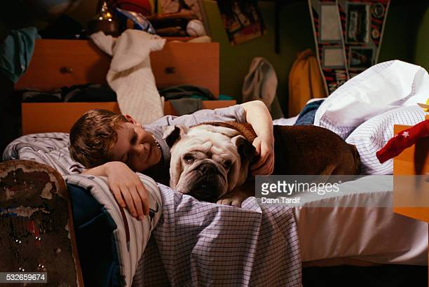 Boy Relaxing in Bed with Bulldog