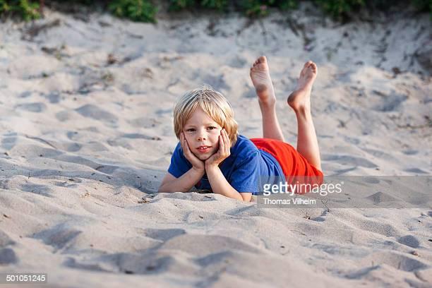 boy relaxing in the sand on the beach - soles pose stockfoto's en -beelden