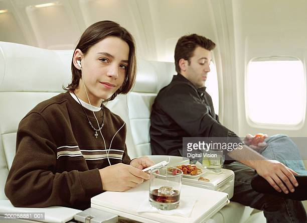 Boy (10-12) relaxing on aeroplane, smiling, portrait