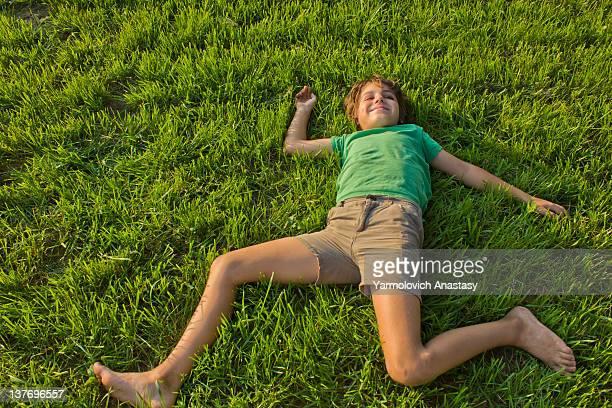 Boy relaxing on green grass lawn