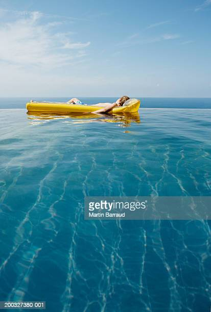 Boy (9-11) relaxing on inflatable raft in infinity pool
