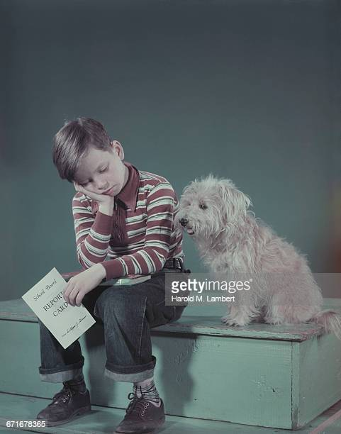 boy relaxing on table while holding report card  - westers schrift stockfoto's en -beelden